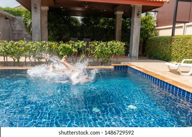 Jump into the pool water, lots of splashes. Happy holidays in the tropics by the warm pool with blue water. Doing sports jumping into the pool with the whole family. Family holiday in Phuket, Thailand