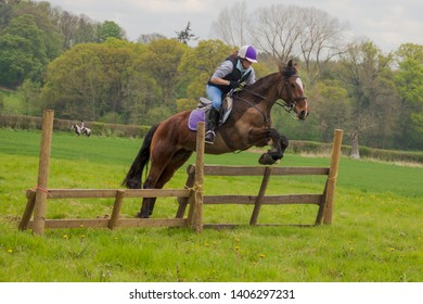 Jump for Joy- A young rider and her horse jump over a large jump in a field.