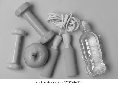 Jump rope, apple and barbells next to water bottle. Health regime and fitness symbols. Dumbbells and skipping rope in cyan and pink color on blue background, top view. Fit shape and sport concept