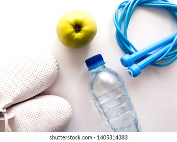 a jump rope apple a bottle of water and sneakers