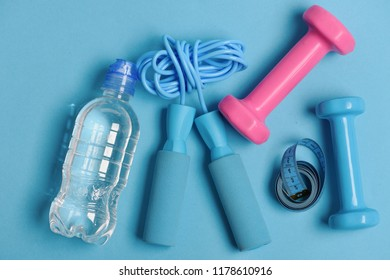 Jump rope and barbells next to water bottle and measure tape. Fit shape and sport concept. Health regime and fitness symbols. Dumbbells and skipping rope in cyan and pink color on blue background