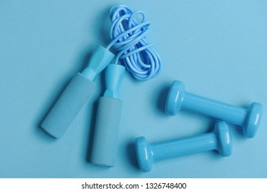 Jump rope and barbells placed next to each other. Health regime and fitness symbols. Dumbbells and skipping rope in cyan color on blue background, top view. Healthy lifestyle and sports concept