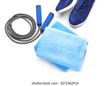 Jump rope, sneakers and clean towel on white background