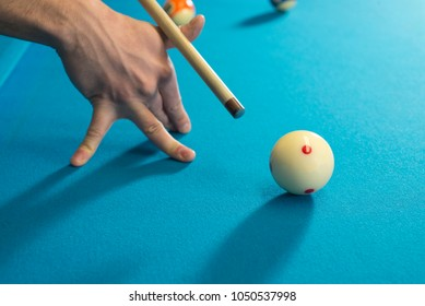 A jump shot over the green ball, shot on 9 ball, on a blue cloth on a pool, billiard table. Close up of a hand with cue aiming on the red dot. Side photo.