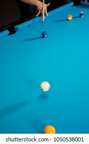 A jump shot over the green ball, shot on 9 ball, on a blue cloth on a pool, billiard table