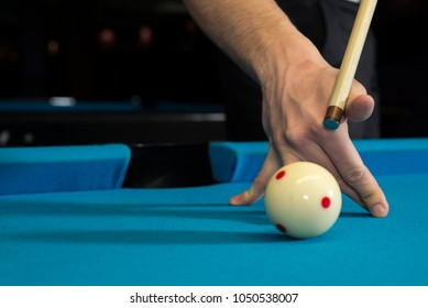A jump shot over the green ball, shot on 9 ball, on a blue cloth on a pool, billiard table. Close up of a hand with cue aiming on the red dot. Extra close up.