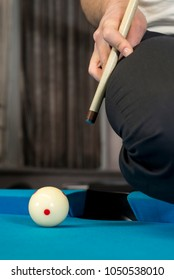 A jump shot over the green ball, shot on 9 ball, on a blue cloth on a pool, billiard table, side shot of jump cue.