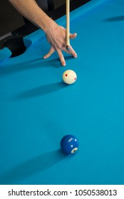 A jump shot over the green ball, shot on 9 ball, on a blue cloth on a pool, billiard table. Close up of a hand with cue aiming on the red dot. Distance photo.