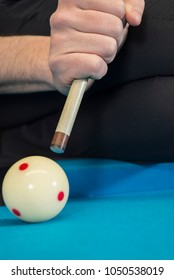 A jump shot over the green ball, shot on 9 ball, on a blue cloth on a pool, billiard table, close up of the shot.