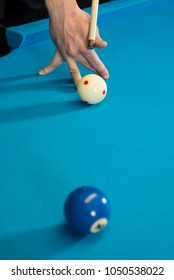 A jump shot over the green ball, shot on 9 ball, on a blue cloth on a pool, billiard table. Close up of a hand with cue aiming on the red dot. Front photo.
