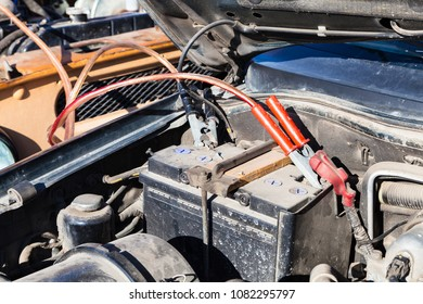 Jump start a flat car battery with another vehicle and jumper leads outdoor