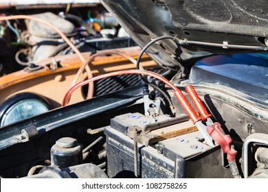 Jump starting a old car battery with another vehicle and jumper leads outdoor