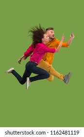 Jump of young couple over green studio background using laptop or tablet gadget while jumping. Runnin girl and man in motion or movement. Human emotions and facial expressions concept. Gadget in