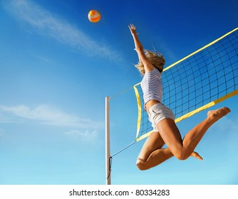 Jump of young girl, playing volleyball on beach.