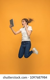 Jump of young woman over orange studio background using laptop or tablet gadget while jumping. Runnin girl in motion or movement. Human emotions and facial expressions concept. Gadget in modern life