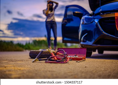 Jumper electric cable and belonging tools prepare by woman driver, need help and assistant at dark of the night, scary and worry alone in the dark, car engine failure or tire need replacement