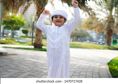 Jumping Arab Saudi Emirati child with happy face on park background wearing traditional Middle Eastern Kandura dress  expo 2020 venue