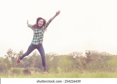 a jumping asian woman feel very happy in soft focus