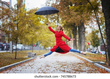 Jumping ballerina with umbrella in one hand. Warm autumn day. Woman in red coat and blue jeans