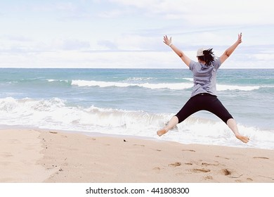jumping at the beach with beautiful cloudy sky
