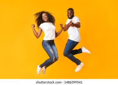 Jumping Black Millennial Couple In The Air, guy pointing at camera, yelllow background