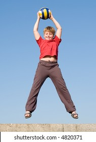 jumping boy with ball on a blue sky
