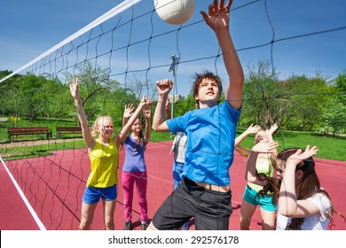 Jumping boy for ball plays volleyball with teens