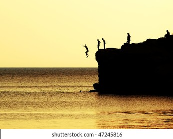 jumping of a cliff at sunset