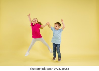 Jumping, dancing. Childhood and dream about big and famous future. Pretty little kids isolated on yellow studio background. Dreams, imagination, education, facial expression, emotions concept.