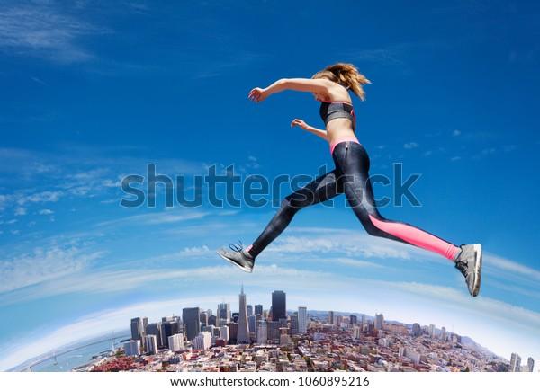 Jumping fit girl across blue sky