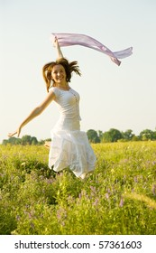 Jumping girl against summer meadow in summer day