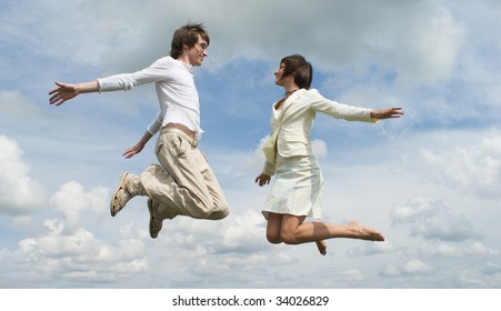 Jumping girl and boy on green meadow