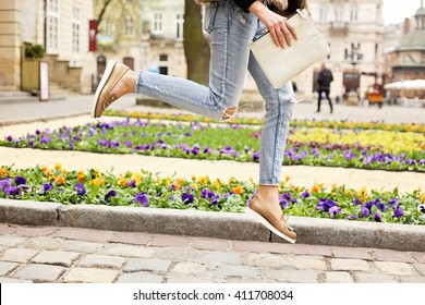 Jumping girl in torn jeans and moccasins on the background of blooming flower beds on the city streets. Summer street fashion look.