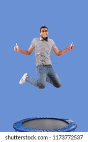 Jumping guy feels happy, thumbs up. Leap on the trampoline high on blue background.
