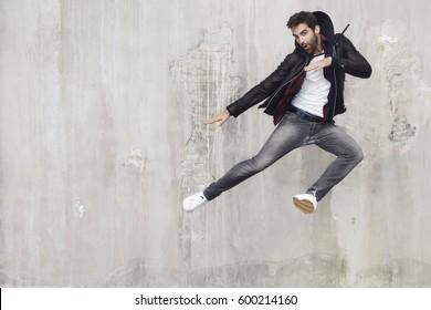 Jumping guy strikes pose in studio