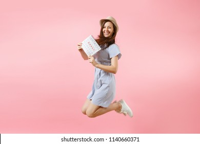 Jumping happy fun woman in blue dress, hat holding periods calendar for checking menstruation days isolated on bright trending pink background. Medical, healthcare, gynecological concept. Copy space