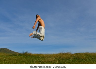 jumping happy young man on a green meadow with blue sky