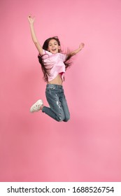 Jumping high. Caucasian little girl portrait isolated on pink studio background. Cute brunette model in shirt. Concept of human emotions, facial expression, sales, ad, childhood. Copyspace.