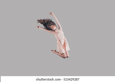 Jumping high. Studio shot of attractive young woman hovering in air
