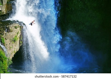 Jumping into the water. Man having fun at waterfalls in the nature. Bali, Indonesia