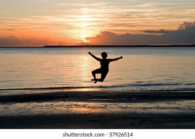 Jumping for joy - a young woman leaping in the air and clicking her heels at sunset, a portrait of joy and celebration