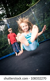 jumping kids on the trampoline in the garden