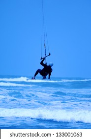 Jumping kite surfer of blue background
