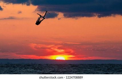 Jumping kitesurfer with a dramatic sunset in the background