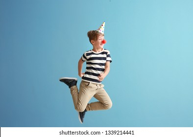 Jumping little boy with clown nose and party hat against color wall. April fools' day celebration