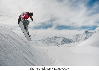 Jumping male snowboarder keeping his one hand on the snowboard on the amazingly beautiful blue sky background