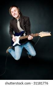 Jumping man with electro guitar, studio shot