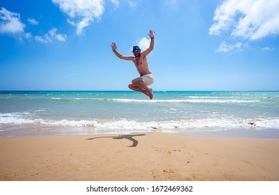 Jumping man with hat on beautiful beach
