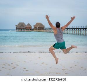 Jumping man on tropical beach