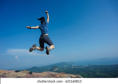 jumping on rocky mountain peak, freedom, risk, challenge, success concept